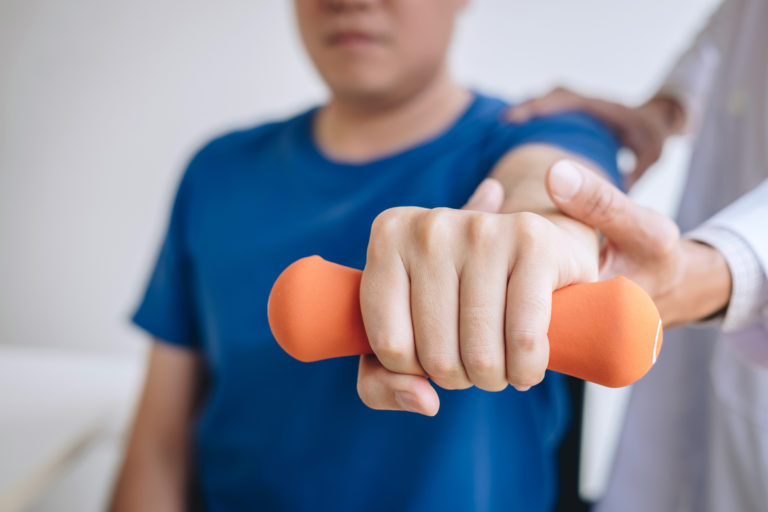 man lifting weight in physical therapy