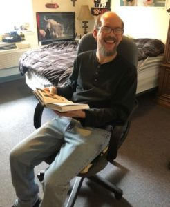 man reading book in his room at Stephens Farm Adeo Brain Injury Services