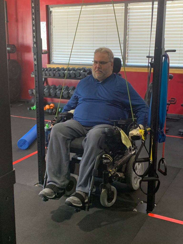 man in wheelchair exercising with bands, adaptive fitness